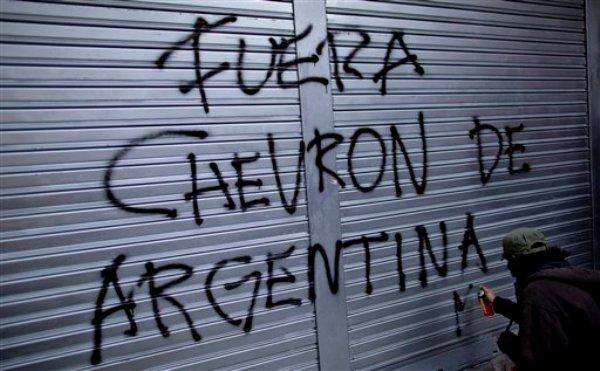 Un manifestante escribe una consigna en una manifestación contra un acuerdo de la YPF argentina y la petrolera estadounidense Chevron, en Buenos Aires, Argentina, el miércoles 28 de agosto de 2013. (AP Photo/Natacha Pisarenko)