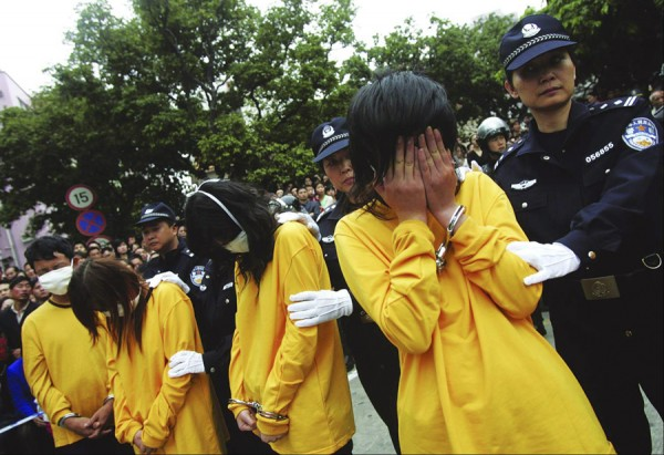Police officers watch over prostitutes during a public parade in Shenzhen
