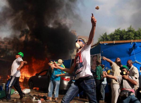 Numerosos manifestantes lanzan piedra contra las fuerzas de seguridad durante una operación llevada a cabo para desmantelar una de las dos acampadas de los simpatizantes del depuesto presidente Mohamed Mursi, cerca de la mezquita de Rabea al Adauiya, en El Cairo (Egipto) hoy, miércoles 14 de agosto de 2013. EFE/Mosaab Elshamy