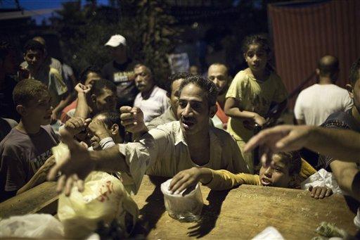 Partidarios del presidente depuesto de Egipto Mohamed Morsi piden comida en una cocina improvisada durante una protesta contra el ejército egipcio cerca de la Universidad de El Cairo en Giza, Egipto, el lunes 5 de agosto de 2013. (Foto AP/Manu Brabo)