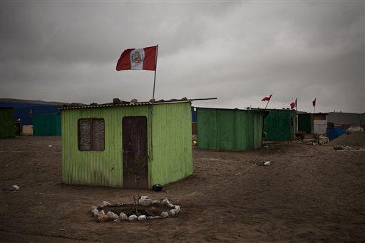 En esta foto de 1 de agosto de 2013, la bandera peruana flamea en una modesta vivienda en las afueras de Lima, Perú. Una ley que data de 1939 exige a todos los hogares peruanos, negocios e instituciones colocar en sitio visible el estandarte nacional desde el 27 al 30 de Julio para honrar el dia de la independencia que se conmemora cada 28 de Julio. (AP Photo/Rodrigo Abd)