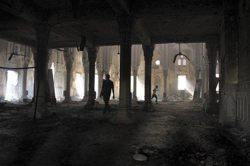 Algunos egipcion caminan entre los restos calcinados de la mezquita Rabá al-Adawiya, en el principal escenario de protestas de los partidarios del derrocado presidente Mohamed Morsi, que fue despejada por las fuerzas de seguridad en el distrito de Nar, en El Cairo, el 15 de agosto del 2013. En la operación hubo más de 500 muertos (AP Foto/Ahmed Gomaa)