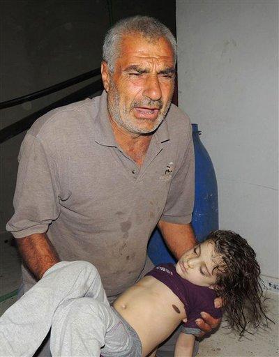 Esta imagen de periodismo ciudadano suministrada por el Comité Local de Arbeen, que ha sido autenticada con base en su contenido y otros reportes de la AP, muestra a un hombre sirio compungido mientras carga el cadáver de una niña siria, luego de un presunto ataque con gas venenoso por parte de las fuerzas armadas del régimen, de acuerdo con activistas del poblado de Arbeen, en Damasco, Siria, el miércoles 21 de agosto de 2013. (Foto AP/Comité Local de Arbeen)