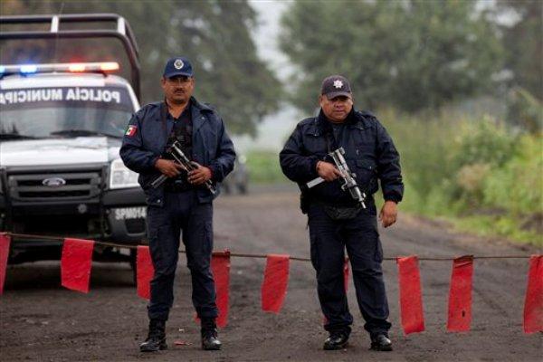 Policías municipales custodian la entrada al Rancho La Mesa, donde las autoridades encontraron una fosa clandesttina en el municipio de Tlalmanalco, México, el jueves 22 de agosto de 2013. (Foto AP/Iván Pierre Aguirre)