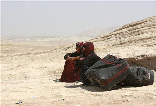 Refugiados sirios descansan al cruzar a Irak en el punto fronterizo de Peshkhabur en Dahuk, 430 kilómetros (260 millas) al noroeste de Bagdad, Irak, el martes 20 de agosto de 2013. Milicias curdas enfrentaron el martes 20 a grupos rebeldes vinculados con al-Qaida en el noreste de Siria, la ronda más reciente de intensos choques que han azuzado un éxodo masivo de civiles al vecino Irak, dijeron activistas.(Foto AP/Hadi Mizban)