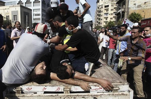 Numerosos manifestantes trasladan a varios heridos durante choques entre simpatizantes de los Hermanos Musulmanes y detractores del depuesto presidente egipcio Mohamed Mursi, cerca de la plaza de Ramsés, en El Cairo (Egipto), hoy, viernes 16 de agosto de 2013.  EFE/Khaled Elfiqi