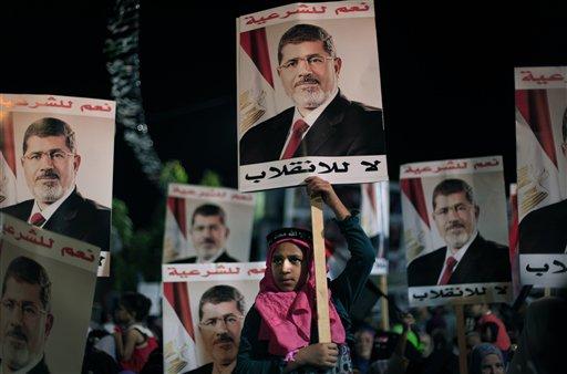 """Simpatizantes del presidente egipcio derrocado Mohamed Morsi  sostienen carteles con texto en árabe que lee """"Sí a la legalidad, no al golpe de Estado"""", durante una protesta afuera de la mezquita Rabaah al-Adawiya, donde los manifestantes han instalado un campamento y sostenido marchas diarias en Nasr City, en el Cairo, Egipto, el martes 6 de agosto de 2013. Más de 10 días de esfuerzos diplomáticos para hallar la forma de resolver el estancamiento en que cayeron la Hermandad Musulmana y el gobierno interino respaldado por el ejército han fracasado, afirmó el miércoles 7 de agosto la presidencia. (Foto AP/Khalil Hamra)"""