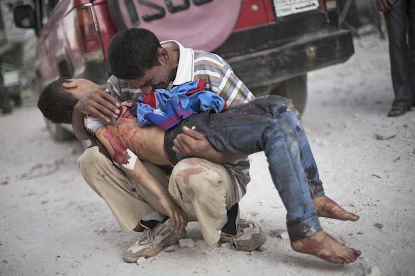ARCHIVO- En esta foto de archivo del 3 de octubre de 2012, un hombre llora mientras sostiene el cuerpo de su hijo, asesinado por el ejército sirio, cerca del hospital Dar El Shifa en Alepo, Siria. El secretario general de las Naciones Unidas Ban Ki-moon dijo el jueves 25 de julio de 2013 que la cifra total de muertos en los dos años y medio de guerra civil en Siria se elevó a más de 100.000. (AP Foto/Manu Brabo, Archivo)