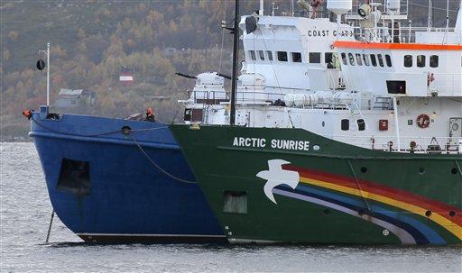 El barco Arctic Sunrice de Greenpeace, a la derecha, permanece detenido en una pequeña bahía cerca de Severomorsk, Rusia, el martes 24 de septiembre de 2013. Según las autoridades rusas, activistas de Greenpeace intentaron subir a una plataforma petrolífera en el Artico. (AP Foto/Efrem Lukatsky)