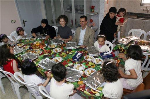 El presidente sirio Bashar Assad (centro) con su esposa, Asma (centro izquierda) comparten la mesa con huérfanos cristianos en el Convento de Santa Tecla en Maaloula, unos 60 kilómertros al noreste de Damasco, en una imagen de 27 de abril de 2008. (Foto AP/Bassem Tellawi, Archivo)