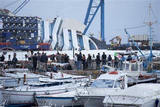 Un grupo de reporteros observan al crucero Costa Concordia ladeado en aguas de la isla toscana de Giglio, Italia, el lunes 16 de septiembre de 2013. (Foto AP/Andrew Medichini)