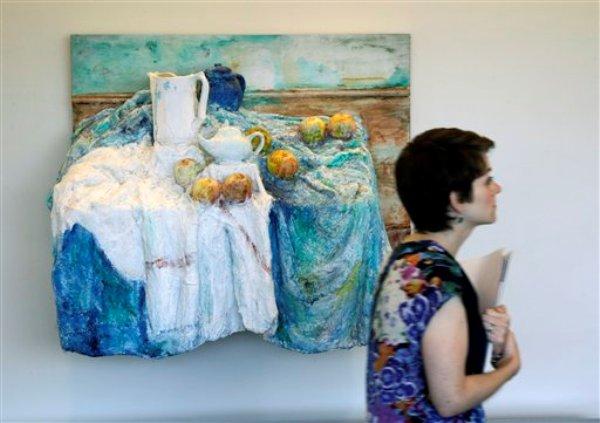 Una visitante pasa junto a una obra tridimensional hecha con vendajes por el artista George Segal, basada en una serie de cuadros de Paul Cezanne, que cuelga en las oficinas centrales de Johnson & Johnson en New Brunswick, Nueva Jersey. (AP Photo/Mel Evans, File)