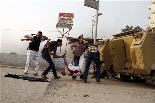 Fuerzas de seguridad egipcias cargan el cadáver del jefe de la policía de Guiza, general Nabil Farag, centro, quien murió cuando combatientes no identificados dispararon contra los efectivos desplegados la mañana del jueves 19 de septiembre de 2013 en el poblado de Kerdasa para expulsar a presuntos islamistas que se apoderaron de la ciudad cercana a las pirámides de Guiza, en Egipto. (Foto AP/Ahmed Abdel Fattah)