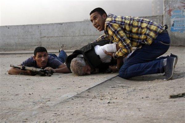 Fuerzas de seguridad egipcias junto al cadáver del general de la Policía de Giza Nabil Farrag, centro, muerto por desconocidos a primeras horas de la mañana en la aldea de Kerdasa, cerca de las Pirámides de Giza en Egipto el jueves, 19 de septiembre del 2013. (Foto AP/Ahmed Abdel Fattah)