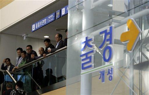 """Trabajadores y directivos surcoreanos esperan para salir del complejo industrial de Kaesong en la oficina Intercoreana de Tránsito, cerca del poblado de Panmunjom, ubicado en la frontera entre Corea del Norte y Corea del Sur desde la Guerra de Corea, el lunes 16 de septiembre de 2013. Ambas naciones llegaron a un acuerdo para reiniciar las operaciones del parque, que dirigen en forma conjunta, cerrado desde abril debido a las tensiones por las amenazas de Pyongyang de lanzar un ataque nuclear. El letrero dice """"Salida"""". (Foto de AP/Lee Jin-man)"""