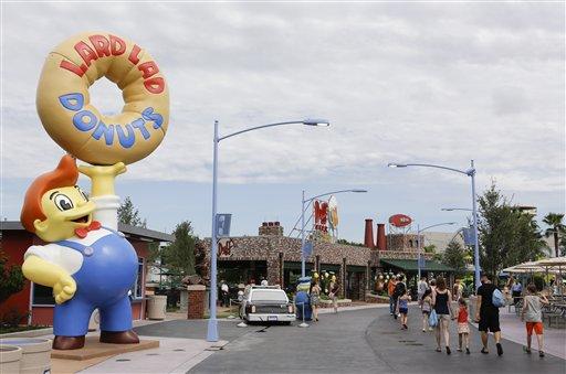 """Visitantes pasan frente a la tienda de rosquillas Lard Lad Donuts, izquierda, y los Jardines Duff en la zona temática Springfield USA en los Estudios Universal en Florida, el jueves 5 de septiembre de  2013, en Orlando, Florida. Creada alrededor del juego mecánico de """"Los Simpson"""" que se inauguró en 2008 la nueva zona del parque tiene comida sabrosa pero insalubre que aparece en el programa. (Foto AP/John Raoux)"""
