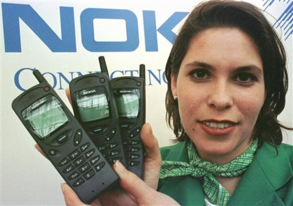 Tania Stefezius sostiene varios teléfonos móviles Nokia 3100 en la muestra CeBUT de 1997 en Hanover, Alemania, en una imagen del 12 de marzo de 1997. Nokia, la otrora estrella de los móviles y orgullo nacional de Finlandia, quedó estremecida el martes 3 de septiembre por la noticia de que  Microsoft Corp. comprará sus operaciones de telefonía móvil. (Foto AP/Fabian Bimmer, archivo)