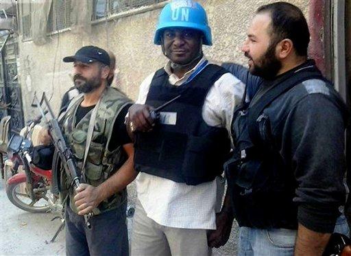 Un miembro del equipo de investigadores de la ONU es escoltado por los rebeldes sirios en Zamalka, una ciudad de las afueras de Damasco, Siria, el miércoles 28 de agosto del 2013, en una foto tomada por un periodista ciudadano cuyo contenido ha sido verificado. En lo que respecta a Siria, el gobierno del presidente Barack Obama está seguro de algo:  El gobierno de su homólogo Bashar Assad debe recibir castigo después que presuntamente usó armas químicas, posiblemente gas sarín, para matar a cientos de sirios. (Foto AP/Oficina de United media de Arbeen)