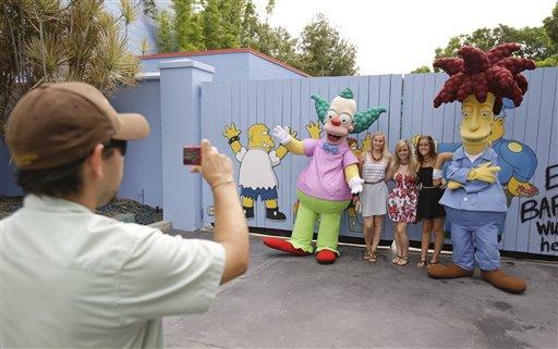 """Un empleado toma fotografías a visitantes junto a personajes de la serie animada """"Los Simpson"""" en la zona temática Springfield USA en los Estudios Universal en Florida, el jueves 5 de septiembre de  2013, en Orlando, Florida. Creada alrededor del juego mecánico de """"Los Simpson"""" que se inauguró en 2008 la nueva zona del parque tiene comida sabrosa pero insalubre que aparece en el programa. (Foto AP/John Raoux)"""