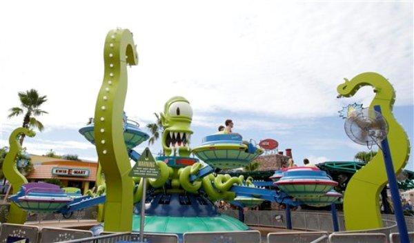 """Visitantes en la atracción Twirl and Hurl en la zona temática Springfield USA en los Estudios Universal en Florida, el jueves 5 de septiembre de 2013, en Orlando, Florida. Creada alrededor del juego mecánico de """"Los Simpson"""" que se inauguró en 2008 la nueva zona del parque tiene comida sabrosa pero insalubre que aparece en el programa. (Foto AP/John Raoux)"""