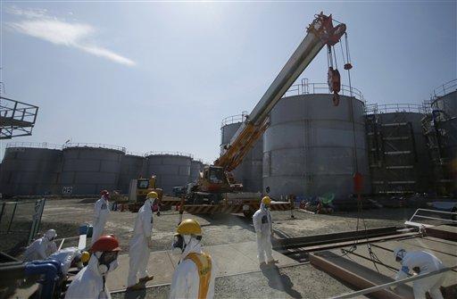 Trabajadores de la operadora Tokyo Electric Power Co. trabajan cerca de tanques de agua radiactiva en la planta nuclear de Fukushima Dai-ichi, en Japón, el 6 de marzo de 2013. El operador de Fukushima, dañada por un sismo y tsunami hace dos años, no ha podido evitar que contaminada se siga filtrando al mar, se informó el martes 6 de agosto de 2013. (Foto AP/Issei Kato, Pool, Archivo)