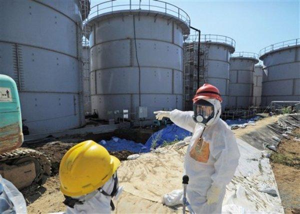En esta foto del 26 de agosto del 2013 el ministro de comercio japonés, Toshimitsu Motegi, der., inspecciona los tanques de la planta nuclear Dai-ichi en Fukushima. El 5 de septiembre, el director de la Autoridad Reguladora Nuclear, Shunichi Tanaka, censuró al operador de la averiada planta nuclear por suministrar datos y explicaciones inadecuados sobre los crecientes derrames de agua radiactiva y contaminada (AP Foto/Kyodo News, File) JAPAN OUT, MANDATORY CREDIT