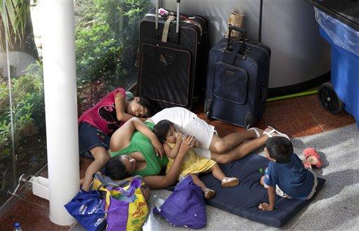 Una familia descansa en un albergue mientras espera ser trasladada a otro lugar, al sur de Acapulco, en Punta Diamante, Mexico, el miércoles 18 de septiembre de 2013.Residentes de Mochitlan, debido a la caida de puentes y destrucción de caminos portan sus pertenencias y víveres a traves de una colina en las afueras de Chilpancingo, Mexico, el miércoles 18 de septiembre de 2013.  El número de fallecidos por las tormentas Ingrid y Manuel que golpearon a México por ambos lados aumentó el miércoles a 80, más de la mitad de ellos en el estado sureño de Guerrero. (AP Photo/Eduardo Verdugo)