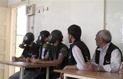 Esta imagen tomada de un video de la AP publicado el miércoles 18 de septiembre de 2012, muestra a estudiantes en Alepo, Siria, con máscaras antigás durante una sesión informativa sobre cómo actuar durante un ataque con armas químicas. (Foto AP vía AP video)