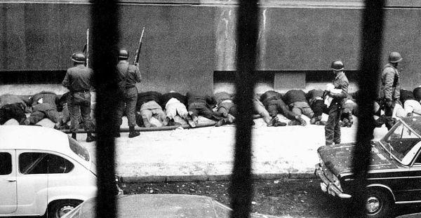 Empleados del Palacio de La Moneda son obligados a arrodillarse contra la pared en una acera, tras ser detenidos por soldados de las Fuerzas Armadas chilenas durante el golpe de Estado de 1973. AP