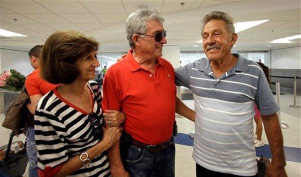 Fotografía del 11 de septiembre de 2013, de Benito Pérez (derecha) sonriendo mientras habla con sus amigos Rogelia (izquierda) y Luis Ventura (al centro) tras la llegada de Pérez al aeropuerto internacional de Miami. (Foto AP/Alan Díaz)
