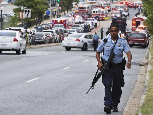 Un agente de la policía metropolitana camina cerca de los Astilleros Navales deWashington, después de un ataque a tiros. El encuentro de béisbol entre los Nacionales de esta ciudad y los Bravos de Atlanta se suspendió el lunes 16 de septiembre de 2013 a consecuencia del tiroteo (AP Foto/Jacquelyn Martin)