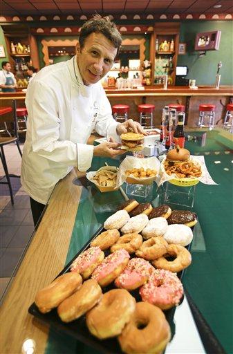 """El chef ejecutivo de Universal Orlando, Steven Jayson, muestra un sándwich de pollo y wafle junto a una Krusty Burger en la taberna de Moe en la zona temática Springfield USA en los Estudios Universal en Florida, el jueves 5 de septiembre de  2013, en Orlando, Florida. Creada alrededor del juego mecánico de """"Los Simpson"""" que se inauguró en 2008 la nueva zona del parque tiene comida sabrosa pero insalubre que aparece en el programa. (Foto AP/John Raoux)"""