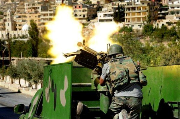 En esta foto de archivo del sábado 7 de septiembre de 2013 divulgada por la agencia de noticias oficial siria SANA, un soldado del ejército sirio dispara artillería pesada durante choques con los rebeldes en la villa Maloul, al noreste de la capital Damasco, Siria. Las tropas sirias lanzaron el lunes 9 de septiembre de 2013 una ofensiva sobre posiciones rebeldes. (AP Foto/SANA, Archivo)