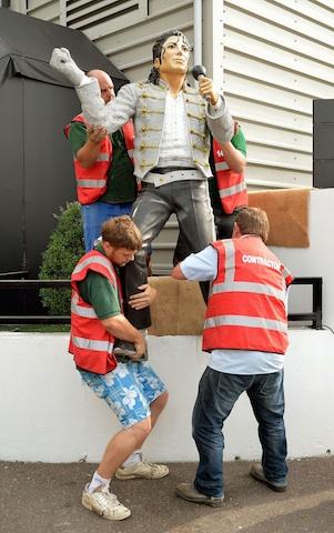 Obreros remueven una estatua de Michael Jackson en el estadio de Fulham, en Londres. (AP Photo/PA, John Stillwell)