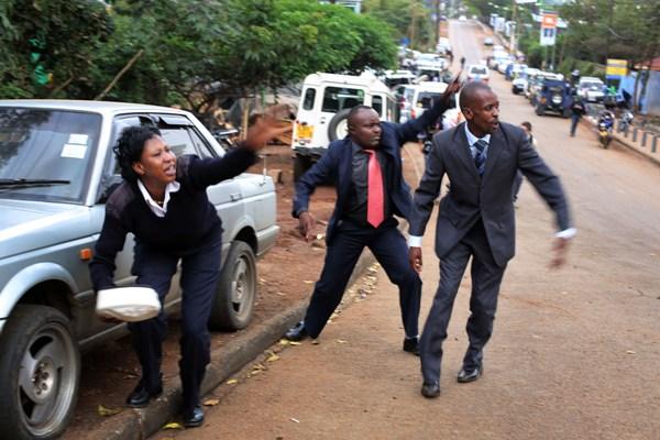 Personal de seguridad de Kenia indica a curiosos que se protejan de las ráfagas de sisparos que salían del centro comercial Westgate, en Nairobi, que el lunes 23 de septiembre de 2013 fue recuperado por el ejército, luego de dos días de cerco. (Foto de AP/ Jerome Delay)