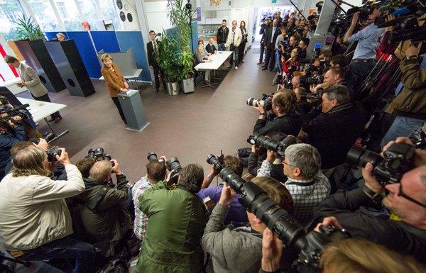 La canciller alemana Angela Merkel, presidenta del partido cristiano demócrata (izquierda), deposita su voto mientras el momento es captado por decenas de representantes de los medios de comunicación en Berlín, el domingo 22 de septiembre de 2013. (Foto AP/Gero Breloer)