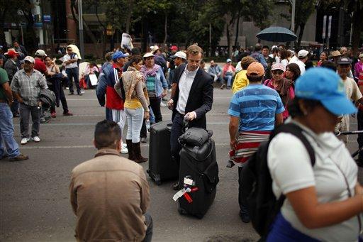 Un hombre con maletas se abre paso a través de un grupo de manifestantes rumbo a un hotel en la Avenida Paseo de la Reforma en la Ciudad de México, el miércoles 4 de septiembre de 2013. Maestros huelgistas continuaron su protesta contra la reforma educativa después de que el Senado la aprobó. (Foto AP/Iván Pierre Aguirre)