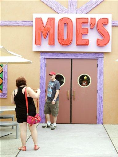 """Visitantes se toman fotografía en la entrada de la taverna de Moe en la zona temática Springfield USA en los Estudios Universal en Florida, el jueves 5 de septiembre de 2013, en Orlando, Florida. Creada alrededor del juego mecánico de """"Los Simpson"""" que se inauguró en 2008 la nueva zona del parque tiene comida sabrosa pero insalubre que aparece en el programa. (Foto AP/John Raoux)"""