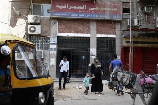 Foto del 21 de septiembre de 2013 que muestra a ciudadanos egipcios pasando  frente al hospital Al-Omraniyah operado por la Asociación Médica de los Hermanos Musulmanes en El Cairo. Un tribunal egipcio ordenó la disolución del grupo y la confiscación de sus activos en un escalamiento de la persecución a los simpatizantes del depuesto presidente Mohamed Morsi. (Foto de AP/Hassan Ammar)