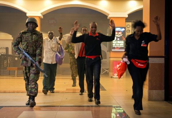 Civiles kenianos que se escondieron durante un intercambio de disparos caminan con las manos en alto como medida de precaución mientras varios policías los conducen a un lugar seguro en el centro comercial Westgate, que fue blanco de un ataque de extremistas somalíes vinculados con al-Qaida en Nairobi, Kenia, el sábado 21 de septeimbre de 2013. (AP Foto/Jonathan Kalan)