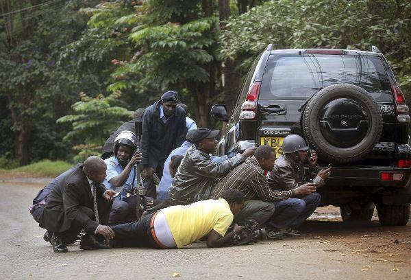 Miembros de los cuerpos de seguridad kenianos buscan refugio detrás de un coche durante el tiroteo con los terroristas. JEROME DELAY (AP)