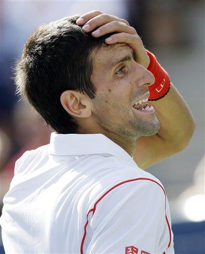 El serbio Novak Djokovic se pone la mano en la frente en expresión de sorpresa durante su partido contra el suizo Stanislas Wawrinka por las semifinales del Abierto de Estados Unidos el sábado 7 de septiembre de 2013. (AP Foto/David Goldman)
