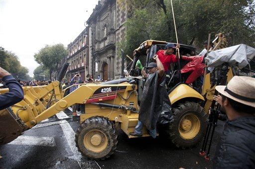 Maestros huelguistas movilizan una excavadora para levantar barricadas ante un posible enfrentamiento con la policía en la Ciudad de México, el viernes 13 de septiembre de 2013. (AP Foto/Eduardo Verdugo)