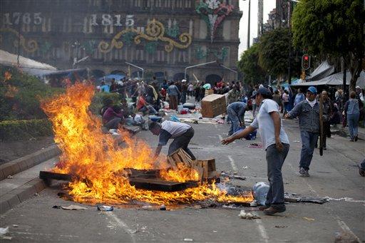 Maestros inconformes prenden fuego a cosas en el Zócalo, la principal plaza de la Ciudad de México, el viernes 13 de septiembre de 2013, en momentos de tensión por un posible enfrentamiento con la policía antidisturbios. (AP Foto/Eduardo Verdugo)