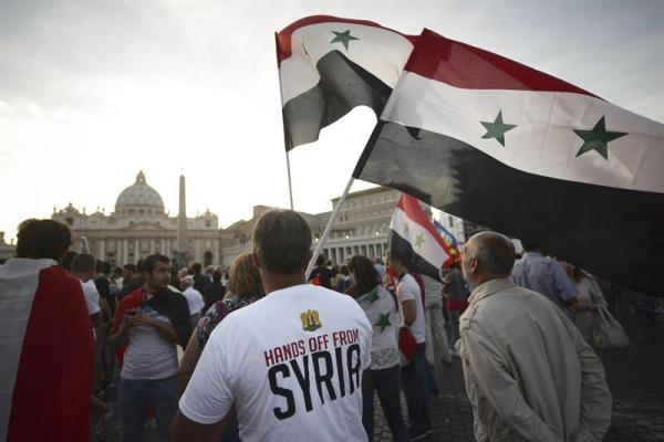 """Un hombre ondea una bandera de Siria y lleva una camiseta con la leyenda """"Manos fuera de Siria"""", en la Plaza de San Pedro, en el Vaticano, el 7 de septiembre de 1013.  EFE/EPA/GUIDO MONTANI"""