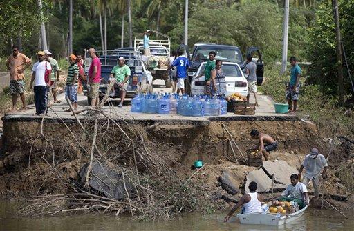 Personas se paran en lo quedó de un puente derribado y esperan lanchas para transportar sus víveres sobre el río Papagayos en la zona sur de Acapulco, Guerrero , el miércoles 18 de septiembre de 2013. El número de fallecidos por las tormentas Ingrid y Manuel que golpearon a México por ambos lados aumentó el miércoles a 80, más de la mitad de ellos en el estado sureño de Guerrero. (AP foto/Eduardo Verdugo)
