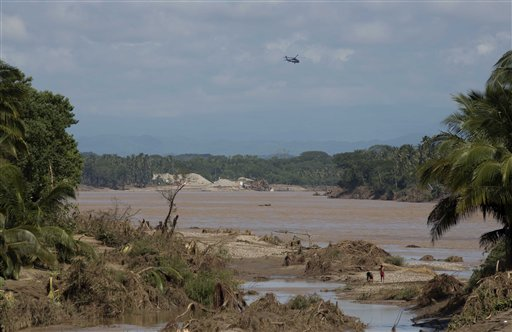 Un helicóptero de la policía federal sobrevuela un río del sur de Acapulco, Guerrero, el miércoles 18 de septiembre de 2013.  Dos tormentas golpearon el estado de guerrero, provocaron deslaves e inundaciones. El número de muertos es 80. (AP foto/Eduardo Verdugo)