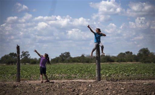 Dos niñas juegan con hondas junto a campos de soja modificada genéticamente en Avia Terai, en la provincia argentina de Chaco, el 31 de mayo del 2013. La biotecnología afianzó a Argentina como exportador de materias primas, pero el rociado de sustancias químicas no sigue las normas de seguridad y contamina viviendas, aulas y el agua. Numerosos médicos dicen que estas sustancias pueden ser las responsables de un aumento en una serie de enfermedades. (AP Photo/Natacha Pisarenko).