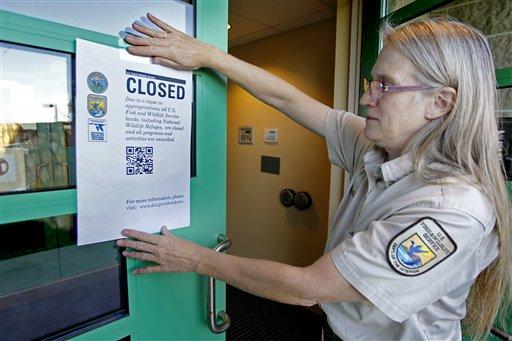 """Jeanne Holler, funcionaria en el Centro de Vida Silvestre del Valle de Minnesota, cuelga un cartel que dice """"Cerrado"""" frente al centro en Bloomington el martes 1 de octubre del 2013. Todos los parques nacionales del estado cierran debido a la paralización de pagos del gobierno estadounidense (AP Foto/Star Tribune, Elizabeth Flores) MANDATORY CREDIT; ST. PAUL PIONEER PRESS OUT; MAGS OUT; TWIN CITIES TV OUT"""