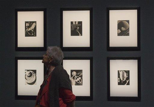 """Una mujer pasa junto a una serie del fotógrafo y pintor Man Ray titulada """"Champs delicious, 1922"""", durante una presentación a la prensa de la exhibición """"Surrealismo y el objeto"""" en el Centro Pompidou de París, el martes 28 de octubre del 2013. La muestra narra por primera vez la historia de cómo los surrealistas canalizaron su mensaje a través de bloques de madera, maniquís y otros objetos filocomunistas de uso cotidiano para cambiarle el rostro al arte del siglo XX, seduciendo a Joan Miró y Pablo Picasso. (AP Foto/Michel Euler)"""
